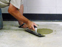 Repairing the cored holes in the concrete slab floor with fresh concrete and cleaning up the Kerrville home.