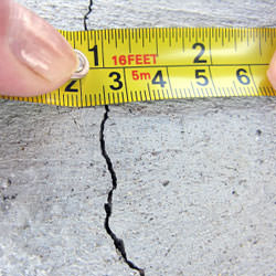 A crack in a poured concrete wall that's showing a normal crack during curing in Cibolo