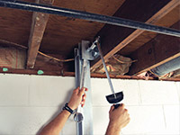 Straightening a foundation wall with the PowerBrace™ i-beam system in a Beeville home.