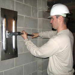installing a wall anchor to repair an bowing foundation wall in Beeville