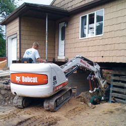Excavating to expose the foundation walls and footings for a replacement job in Boerne